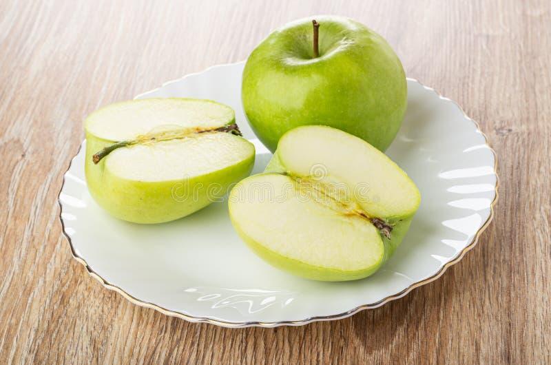 Metà della mela verde, intera mela in piatto bianco sulla tavola immagini stock