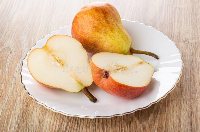 Metà della pera rossa, intera pera in piatto bianco sulla tavola immagine stock libera da diritti