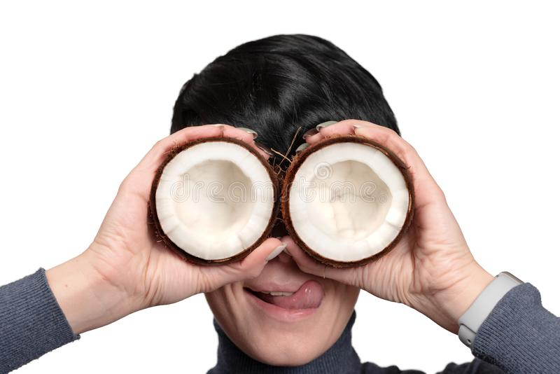 Metà della tenuta due della giovane donna della noce di cocco davanti agli occhi immagine stock libera da diritti