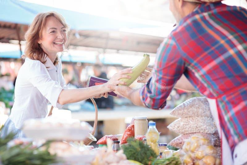 Metà di acquisto sorridente felice della donna adulta per le verdure organiche fresche in un mercato, portante un canestro fotografia stock libera da diritti