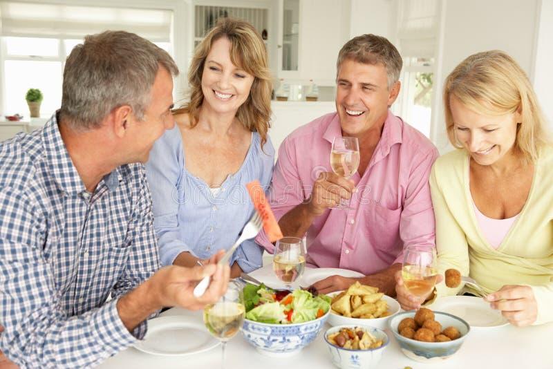 Metà di coppie di età che godono del pasto nel paese immagine stock