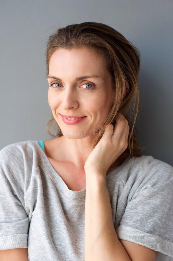 Metà di donna adulta adorabile che sorride con la mano in capelli fotografie stock libere da diritti