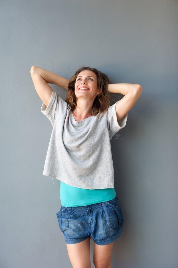 Metà di donna adulta sveglia che sorride con le mani dietro la testa fotografie stock libere da diritti
