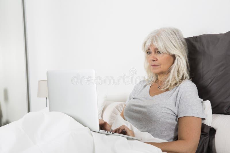 Metà di donna di età con un computer portatile a letto immagini stock libere da diritti