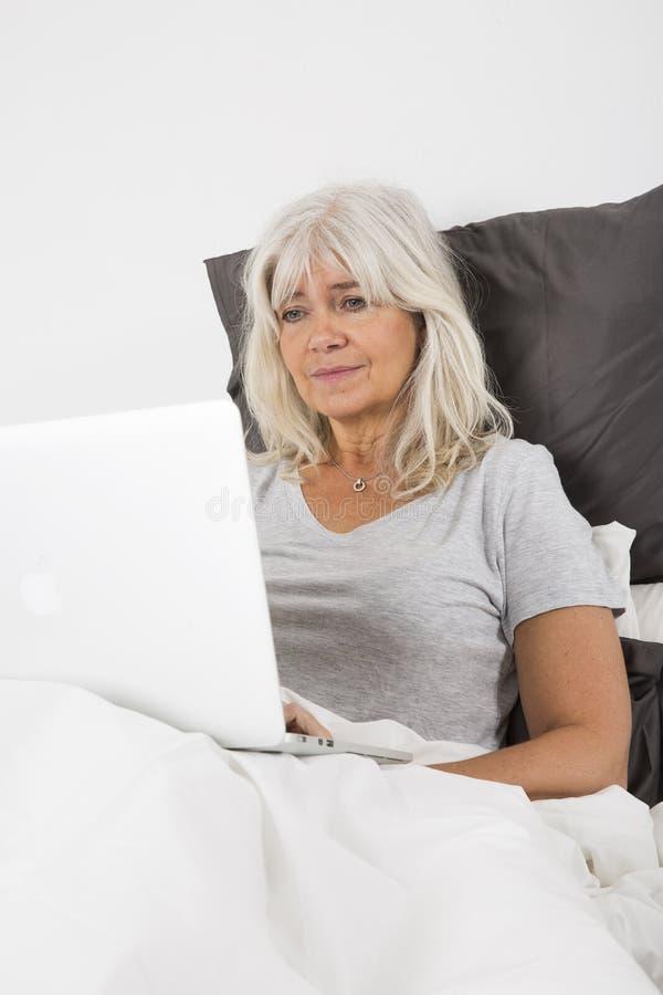 Metà di donna di età con un computer portatile a letto fotografie stock libere da diritti