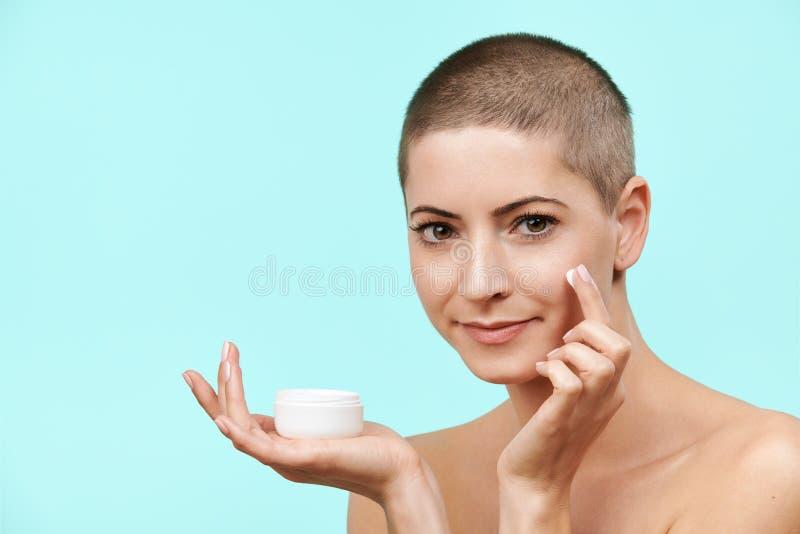 Metà di donna sorridente 30s che applica crema d'idratazione sul suo fronte Foto della donna caucasica attraente con pelle sana fotografia stock