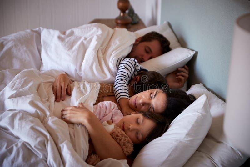 Metà di genitori adulti e loro la menzogne di due bambini piccoli addormentati a letto, vita su, fine su immagini stock