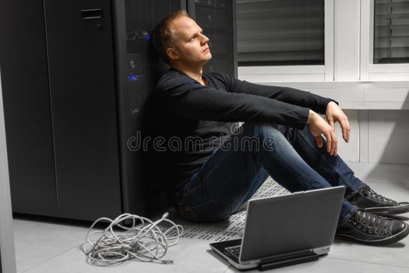 Metà di ingegnere esaurito Against SAN del maschio adulto l'IT al centro dati immagini stock libere da diritti