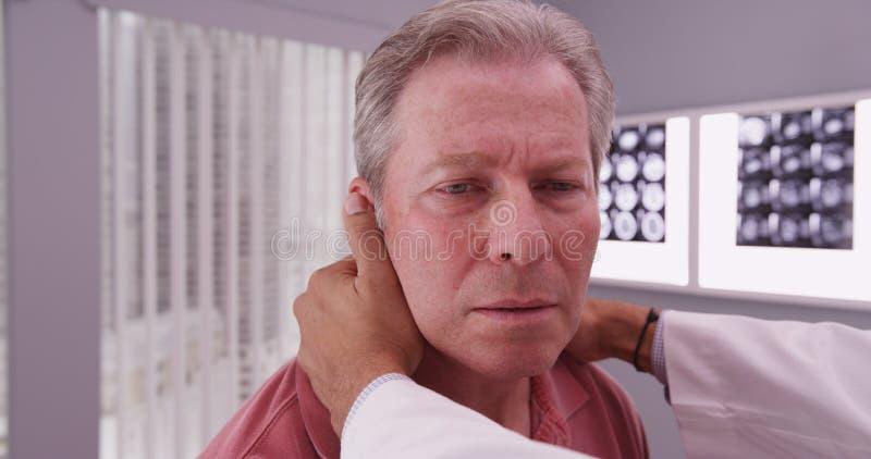 Metà di paziente maschio invecchiato facendo esaminare collo dal medico medico fotografie stock