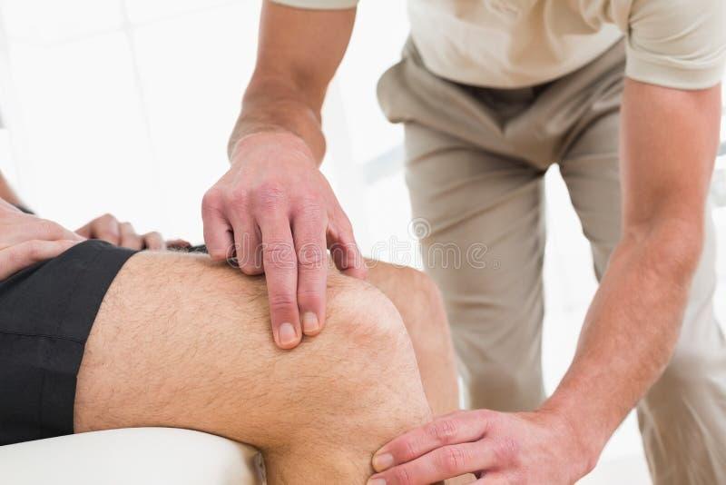 Metà di sezione del primo piano di un uomo che ottiene il suo ginocchio esaminato immagine stock libera da diritti