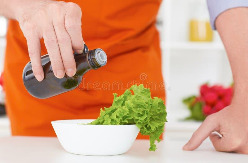 Metà di sezione dell'olio d'oliva di versamento dell'uomo maturo sopra insalata fresca nella cucina del ristorante immagini stock