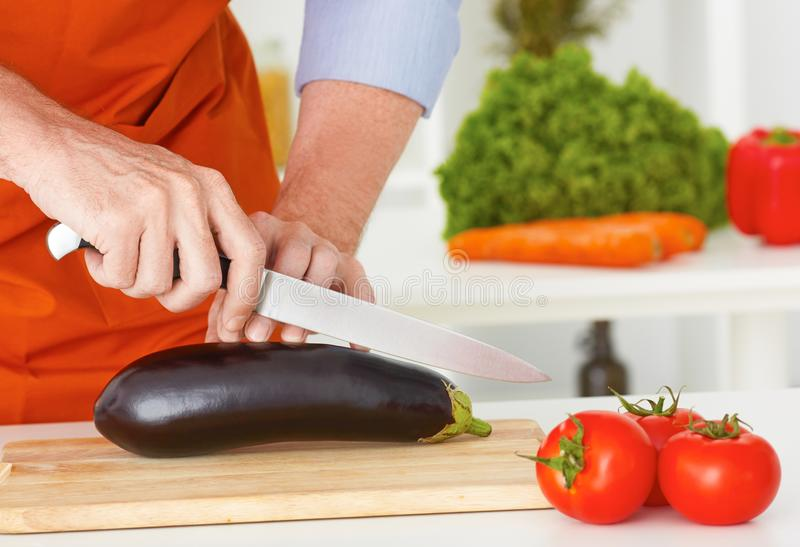 Metà di sezione dell'uomo maturo che prepara tagliare cavolo a pezzi nella cucina a casa fotografia stock