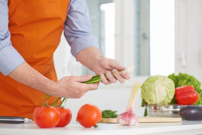 Metà di sezione dell'uomo maturo che prepara tagliare le cipolle a pezzi verdi nella cucina a casa fotografie stock