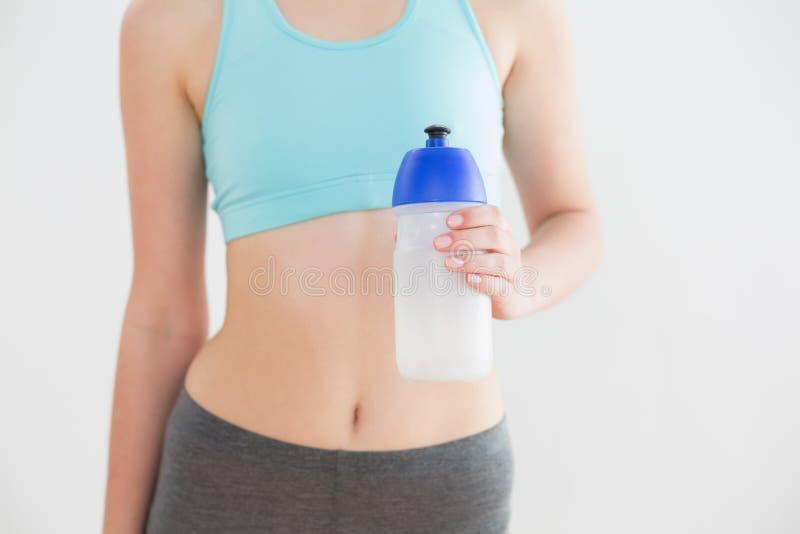 Metà di sezione della bottiglia di acqua della tenuta della donna di misura contro la parete fotografia stock