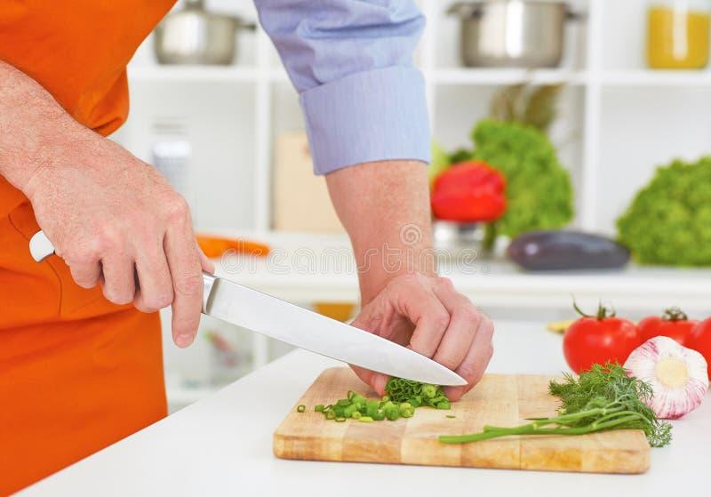 Metà di sezione delle verdure mature di taglio dell'uomo nella cucina fotografie stock libere da diritti