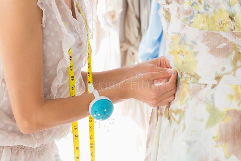 Metà di sezione di uno stilista che lavora al vestito fotografia stock libera da diritti