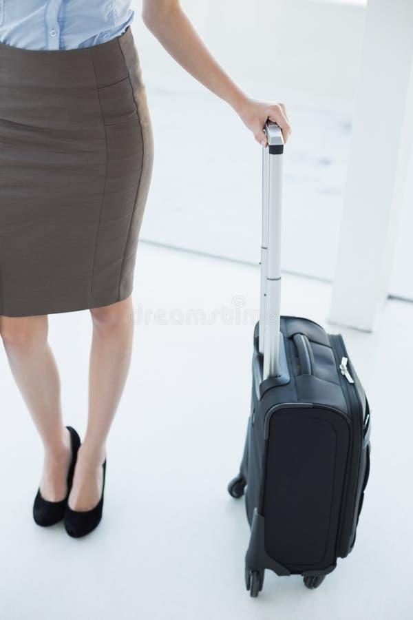 Metà di sezione sulla donna di affari di classe snella che tiene una valigia immagine stock libera da diritti