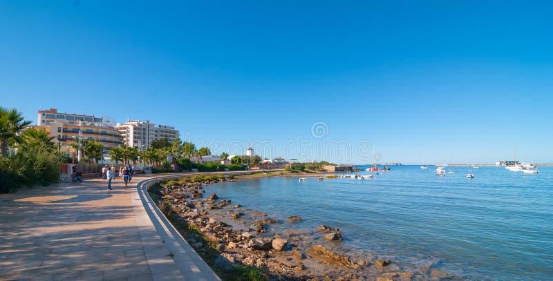 Metà di sole di mattina sulla città della spiaggia Riscaldi il giorno soleggiato lungo la spiaggia in Ibiza, la st Antoni de Port fotografie stock libere da diritti