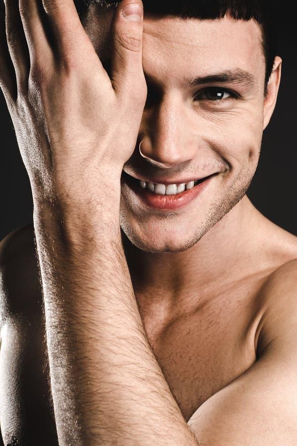 Metà nascondentesi maschio felice del fronte immagine stock