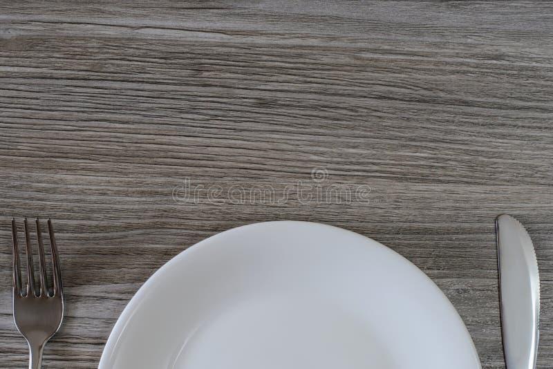 Metà superiore del piatto, del coltello e della forcella vuoti bianchi sulla linguetta di legno grigia fotografia stock