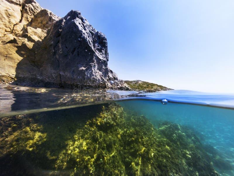 A metà underwater nel mare fotografia stock