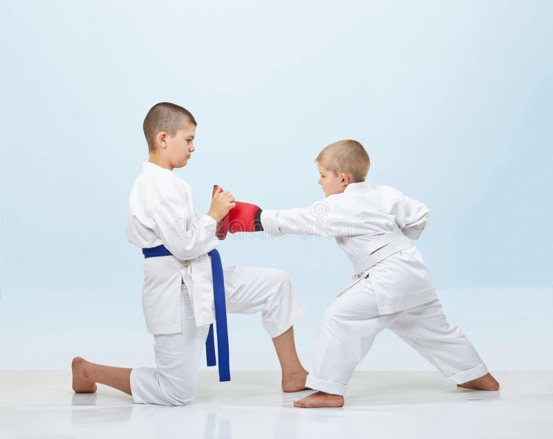 Met bekledingen op handen slaat karateka in karategi stempel op simulators stock afbeeldingen