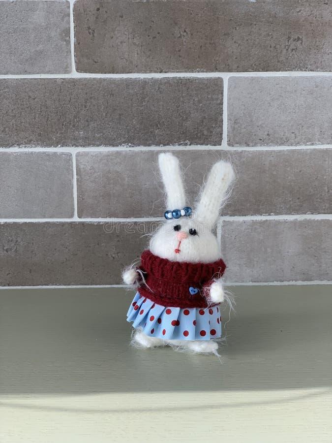 Met de hand gemaakt gebreid stuk speelgoed Paashaas in rode sweater met en blauwe rok Het stuk speelgoed van konijnkerstmis hazen stock foto's