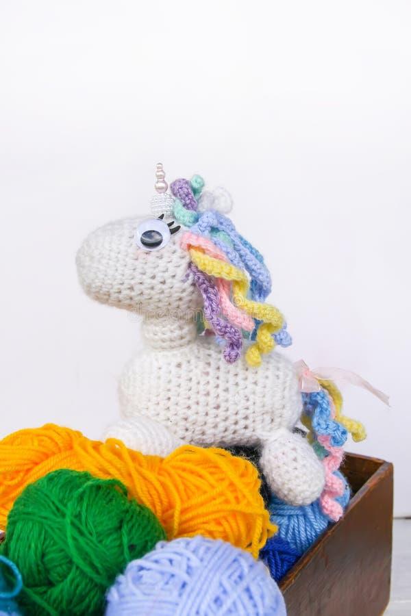 Met de hand gemaakt gehaakt eenhoornstuk speelgoed en garen in een houten doos op witte achtergrond stock fotografie