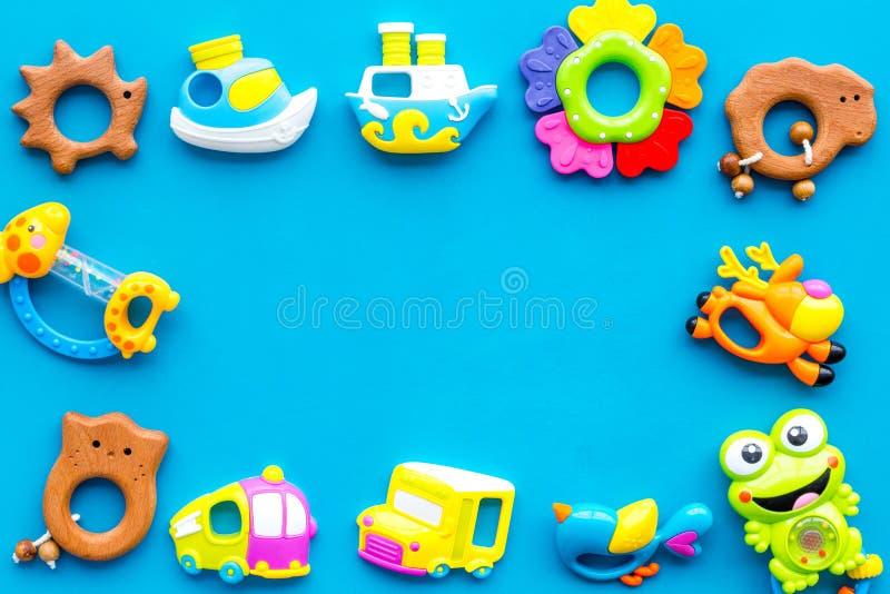 Met de hand gemaakt speelgoed voor pasgeboren babys, plastic en houten rammelaar op blauwe achtergrond hoogste meningsruimte voor royalty-vrije stock afbeeldingen