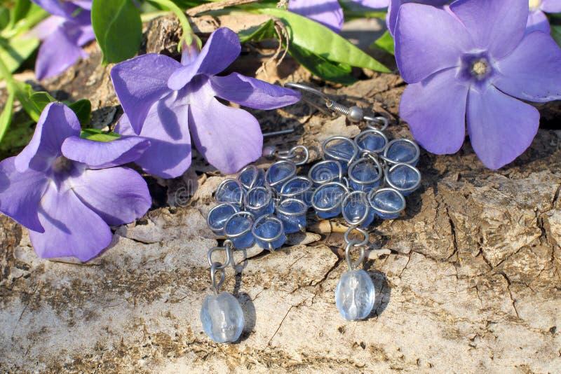 Met de hand gemaakte blauwe glasoorringen op de aardachtergrond stock foto