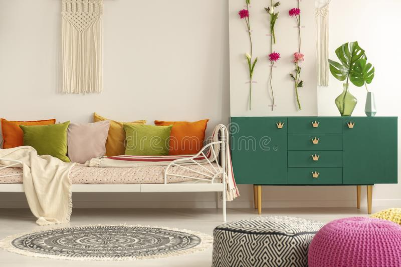 Met de hand gemaakte bloemraad op groen houten kabinet met blad in glasvaas naast comfortabel bed met groene olijf, pastelkleurro royalty-vrije stock foto's