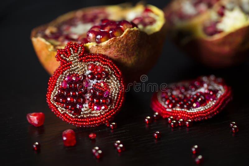 Met de hand gemaakte broche in vorm van granaatappel met rode of karmozijnrode glasparels en gevoeld stock foto's