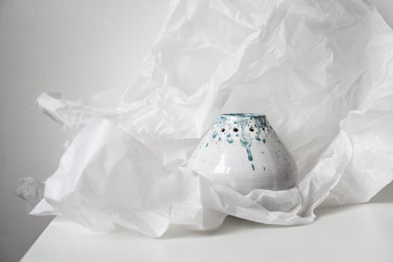 Met de hand gemaakte ceramische vaas op gedeukt Witboek stock afbeeldingen