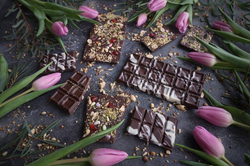 Met de hand gemaakte chocolade met noten en droge vruchten met Roze tulpen, Chocolatier, Zoete giften, de Dag van Valentine, Witt stock afbeelding