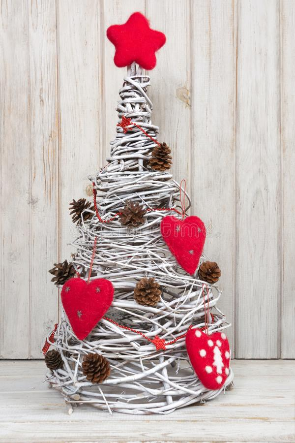 Met de hand gemaakte Kerstboom met rood die hart als decor van wijnstok voor wit binnenland wordt gemaakt stock afbeeldingen