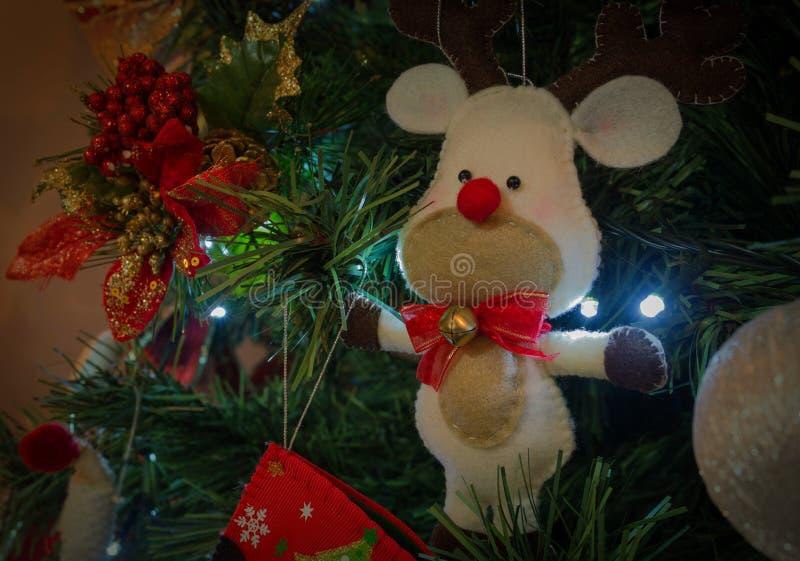 Met de hand gemaakte kinderachtige de karikatuurholding van het stoffenrendier in groen en rode Kerstmisboom stock foto's