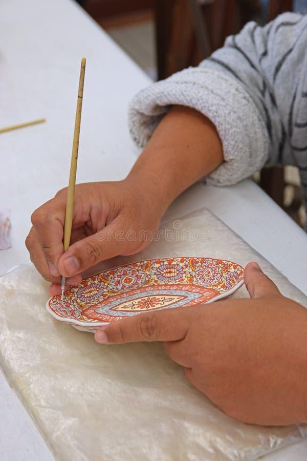Met de hand gemaakte kunst van het schilderen van porseleinplaat die borstel gebruiken stock afbeeldingen