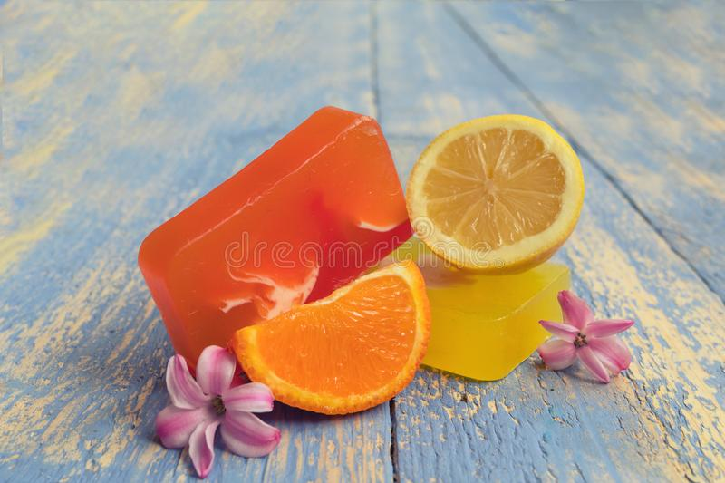 Met de hand gemaakte natuurlijke zeep met natuurlijke ingrediënten: citroenen en sinaasappelen, op rustieke houten raad Kuuroord  stock afbeeldingen
