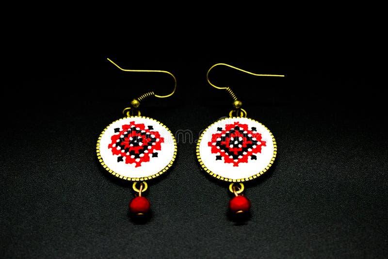 Met de hand gemaakte oorringen met rood en zwart Roemeens traditioneel model Geïsoleerd op Zwarte stock foto's