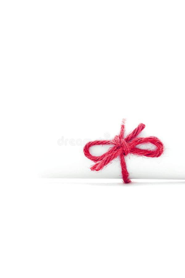 Met de hand gemaakte rode die koordknoop op geïsoleerde Witboekrol wordt gebonden royalty-vrije stock foto's