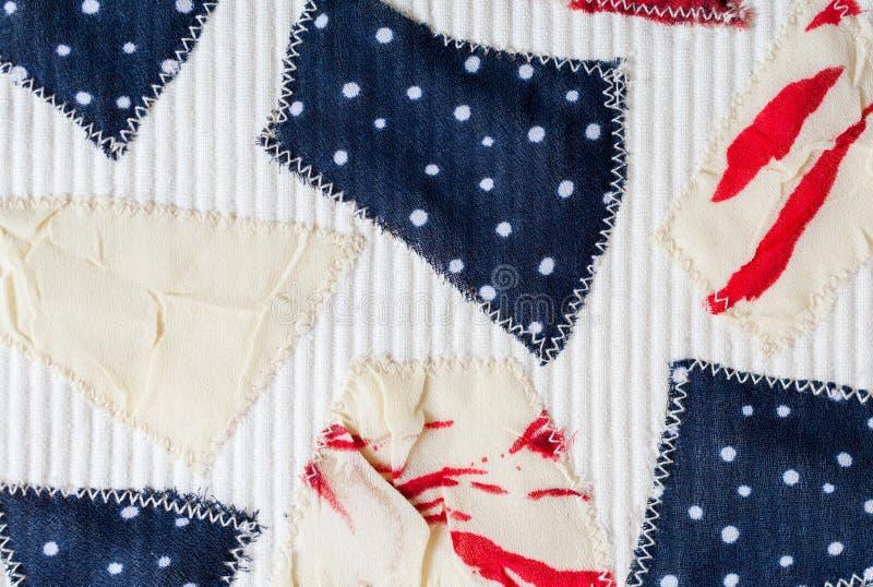 Met de hand gemaakte textielachtergrond met gekleurde stukken verschillende die stoffen op witte stof worden genaaid stock fotografie