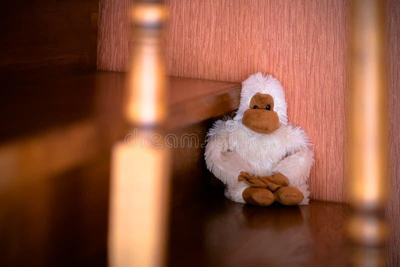 Met de hand gemaakte witte aapstuk speelgoed plaatsing op de bruine houten treden royalty-vrije stock afbeelding