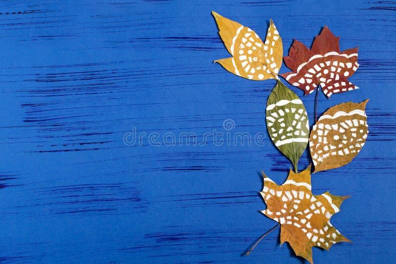 Met de hand geschilderd op droge de herfstbladeren stock foto's