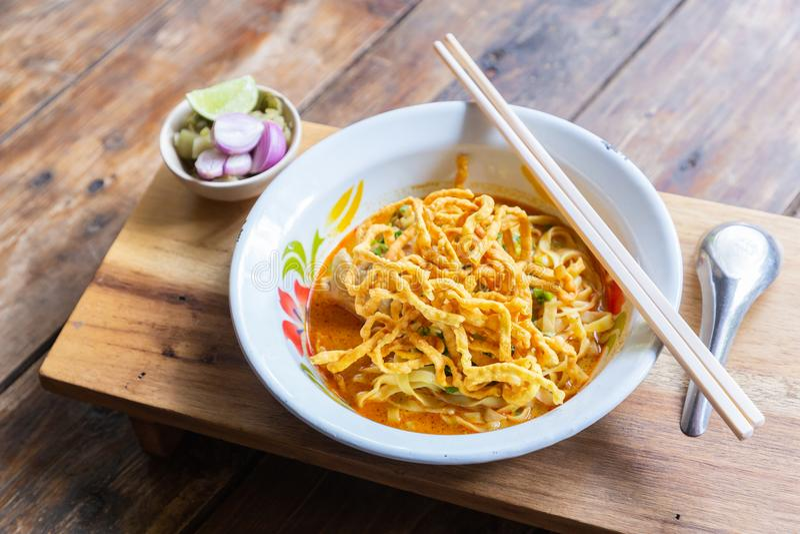 Met kerrie gekruide soi van Khao van de noedelsoep met kippenvlees en kruidige kokosmelk op houten lijst stock afbeeldingen