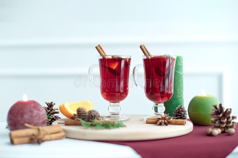Met kerst gemoeide wijn met kaneel, kardamom en anijs op een witte houten achtergrond. Kersttafel met warme drank stock foto's