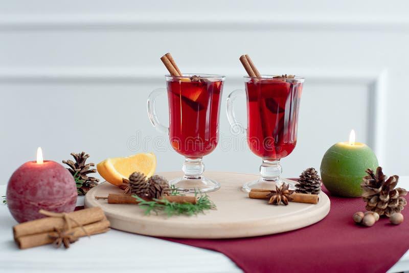 Met kerst gemoeide wijn met kaneel, kardamom en anijs op een witte houten achtergrond. Kersttafel met warme drank stock foto