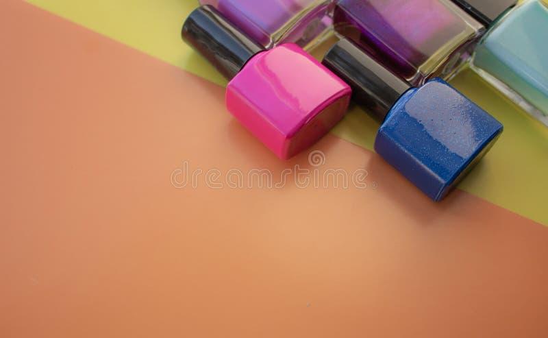 met le vernis à ongles en bouteille Un groupe de vernis à ongles lumineux sur un fond coloré et jaune Avec l'espace vide du côté  photographie stock