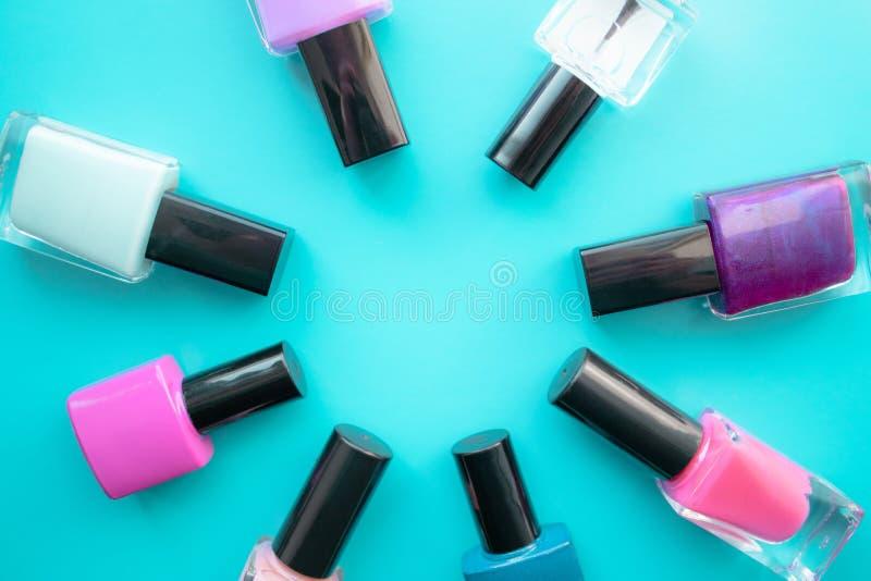 met le vernis à ongles en bouteille Un groupe de vernis à ongles lumineux sur un fond vert Avec l'espace vide au milieu images libres de droits
