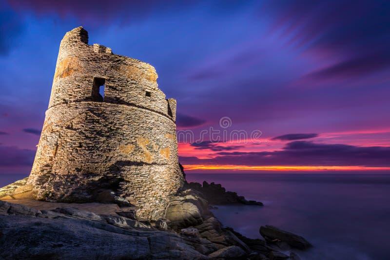 Met schijnwerpers verlichte Genoese-toren in Erbalunga in Corsica bij zonsopgang stock afbeeldingen