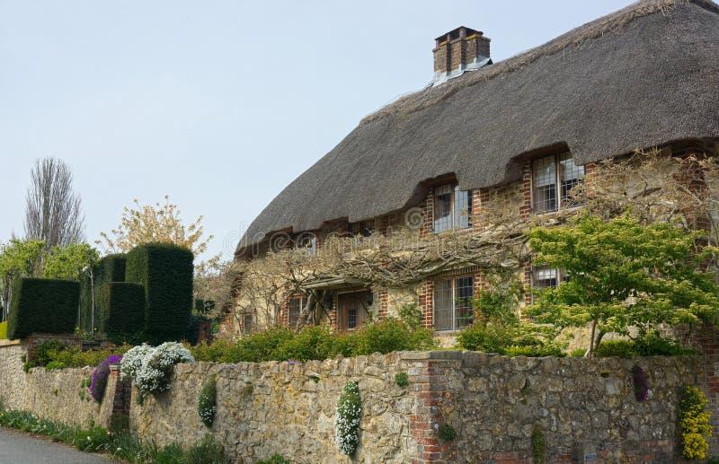 Met stro bedekt roofed plattelandshuisje en ommuurde tuin het UK stock afbeeldingen
